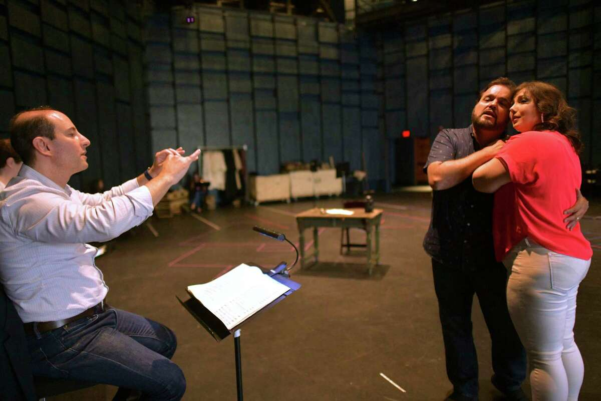 """Francesco Milioto (left) conducts an Opera San Antonio rehearsal of """"Tosca."""" Jennifer Rowley (right) plays the title role and Rafael Davila plays her beloved Cavaradossi."""