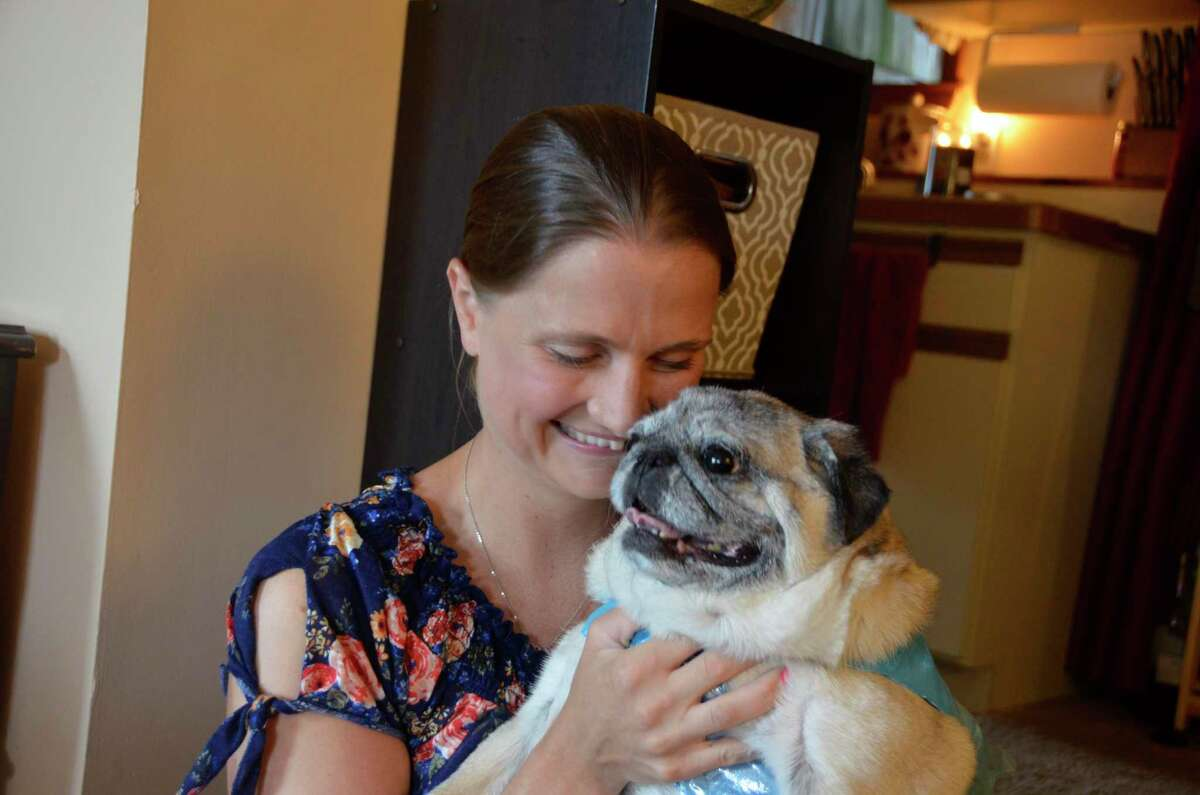 BreAnna Morin hugs her dog Bella, a 9-year-old pug. Bella needs surgery, and Morin has been collecting cans and bottles to pay for it.