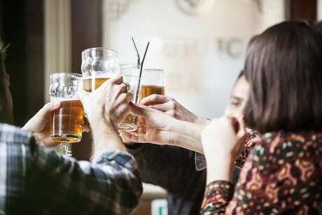 A group of friends toasting with beer mugs at a pub.