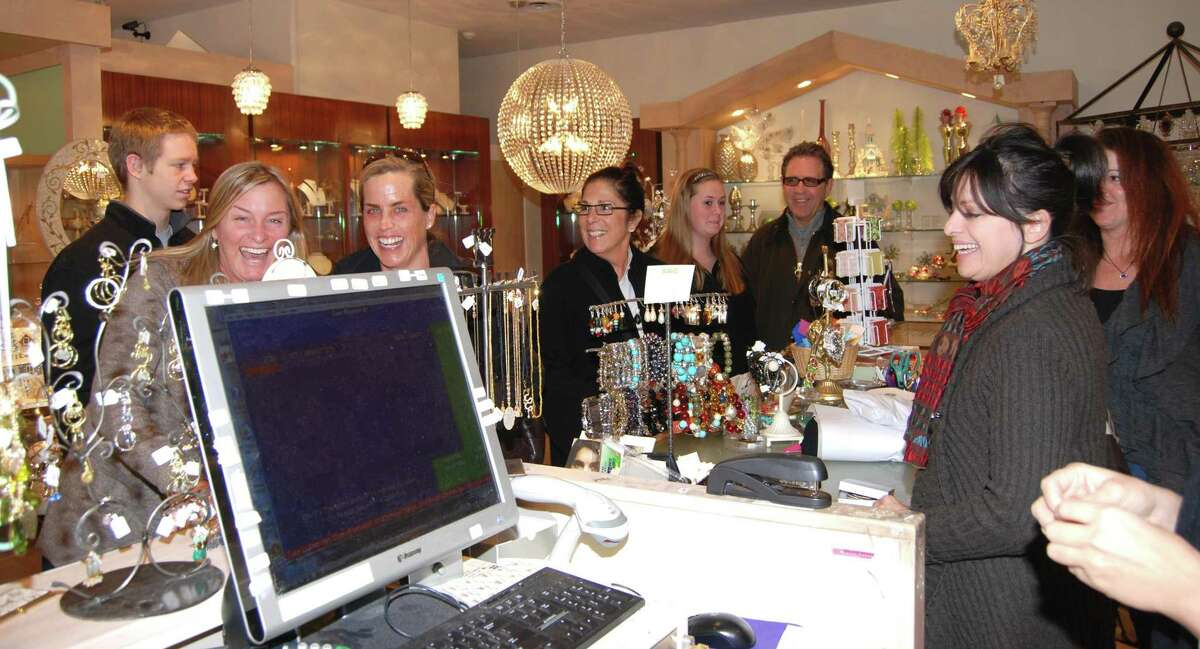 WAVE is the place to be if you want to have fun while shopping...salesperson Dina Keeffe and Bebe Somerby have some laughs while son Mike Somerby (far left), Libby Brost, Mogan Brost, Bob Brost, jewelry designer Carrie Kulawitz and WAVE owner Heather Satin join in!