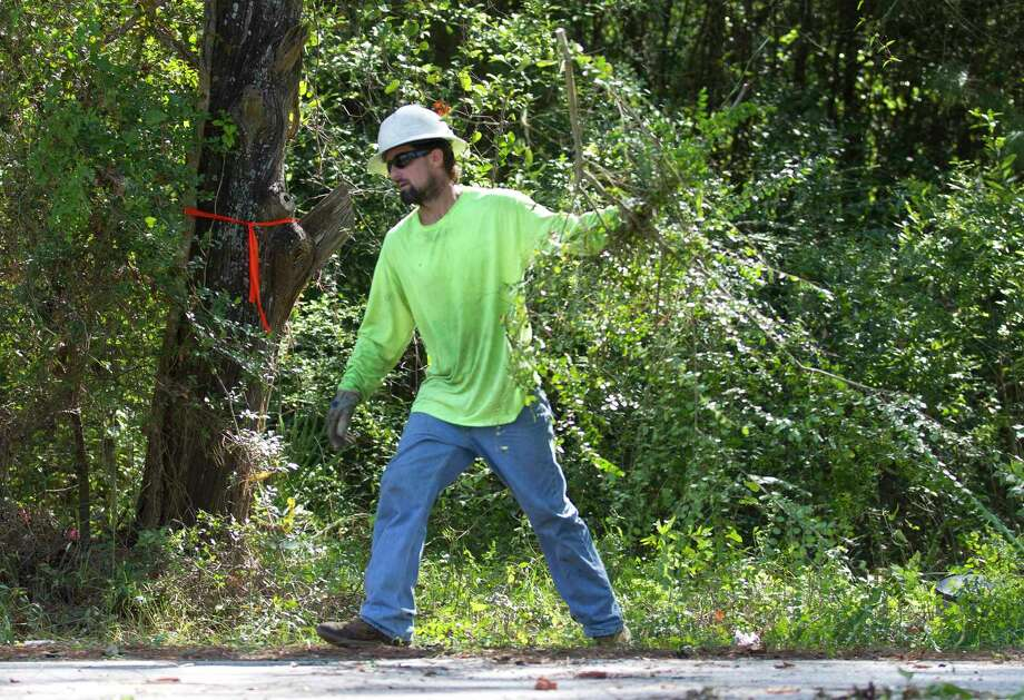 Workers clear the right of way section of North 10th Street in front of the Conroe Community Cemetery between the Oakwood Cemetery and Old Normal College property for a fence to be installed, Tuesday, Sept. 3, 2019, in Conroe. The densely wooded property is the final resting place for dozens of black who settled in Montgomery Coutny during the post Civil War era. Photo: Jason Fochtman, Houston Chronicle / Staff Photographer / Houston Chronicle