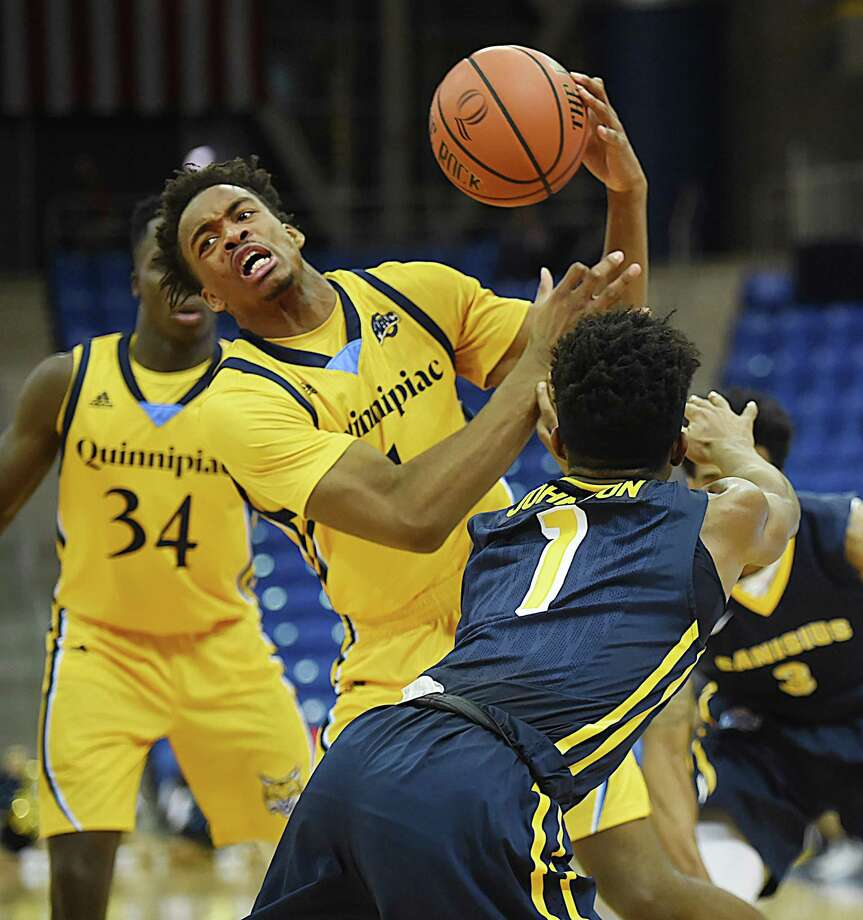 Quinnipiac senior guard Cameron Young is fouled by Canisius sophomore guard Malik Johnson during a game in 2018. Photo: Catherine Avalone / Hearst Connecticut Media / New Haven Register