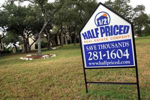 Half Priced Real Estate Company sign, in front of a house in north San Antonio which is listed with them, Wednesday, Aug. 30, 2006. photo Bob Owen