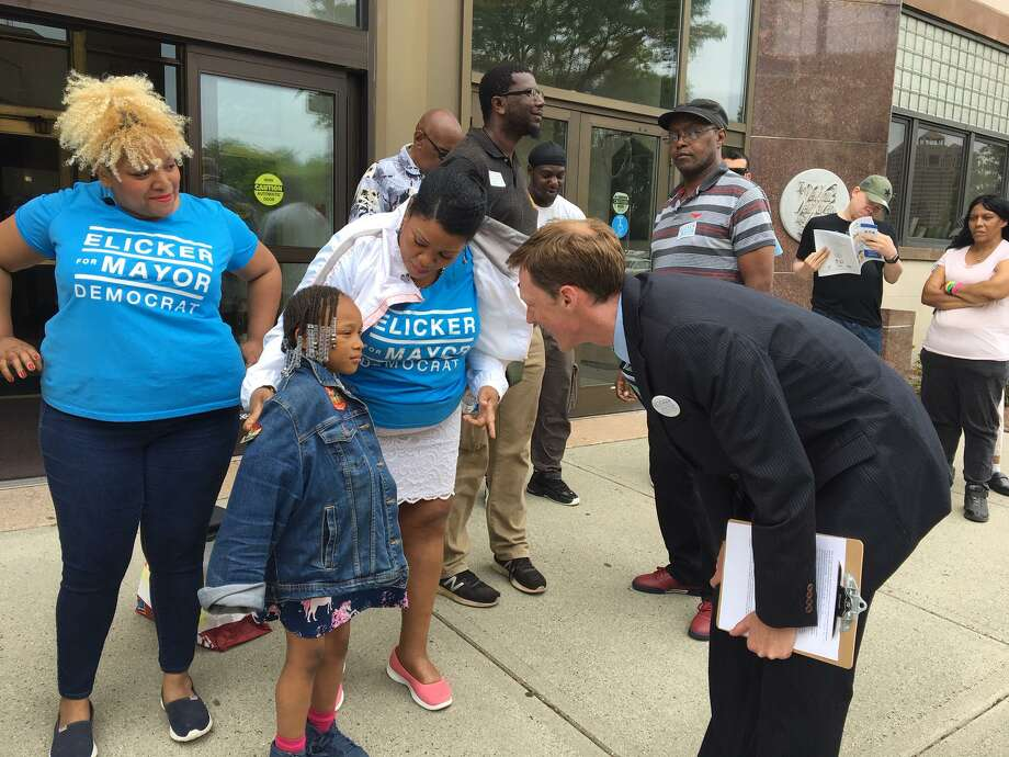 New Haven Mayoral contender Justin Elicker speaks to a young supporter. Photo: Mary E. O'Leary / Hearst Connecticut Media