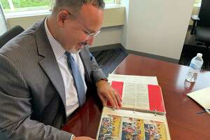 Education Commissioner Miguel Cardona looks over a scrapbook his parents had made at the start of his first year teaching in 1998.
