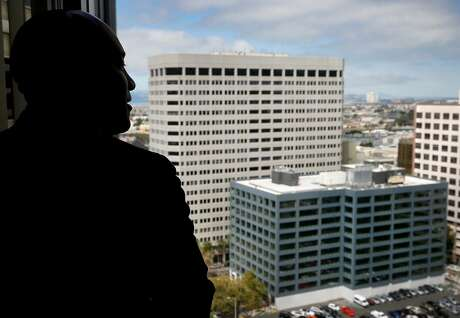 Rodd Lee, Interim Assistant General Manager of External Affairs for BART, views a new office building (lower right) from the 18th floor of the Kaiser Building in Oakland, Calif. on Thursday, Sept. 5, 2019. BART administrators are hoping to relocate the transit agency's longtime headquarters in the Kaiser Center to the newly constructed office building two blocks away on Webster Street.