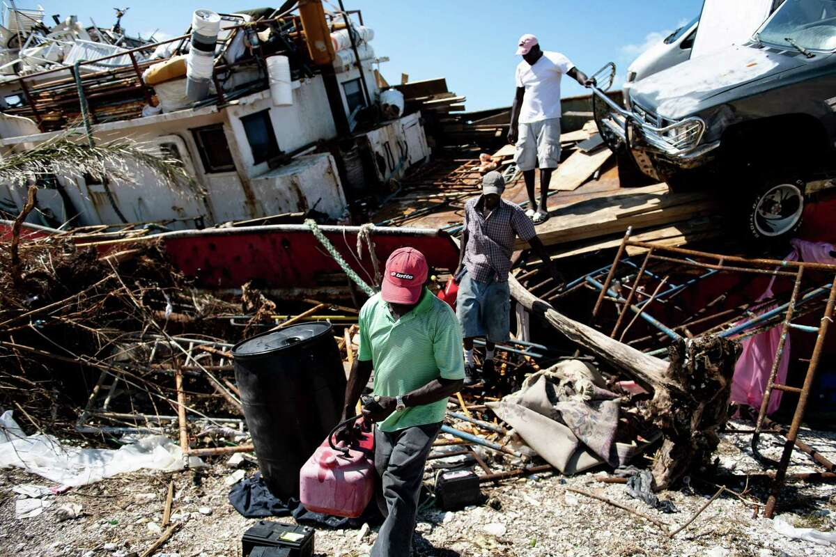 People recover items from a beached boat after Hurricane Dorian September 5, 2019, in Marsh Harbor, Great Abaco. - Hurricane Dorian lashed the Carolinas with driving rain and fierce winds as it neared the US east coast Thursday after devastating the Bahamas and killing at least 20 people. (Photo by Brendan Smialowski / AFP)BRENDAN SMIALOWSKI/AFP/Getty Images