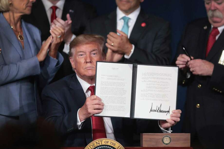President Donald Trump signs a proclamation that will eliminate student loan debt for qualifying disabled veterans following a speech at the American Veterans 75th National Convention Aug. 21 in Louisville, Kentucky. Photo: Scott Olson / Getty Images / 2019 Getty Images