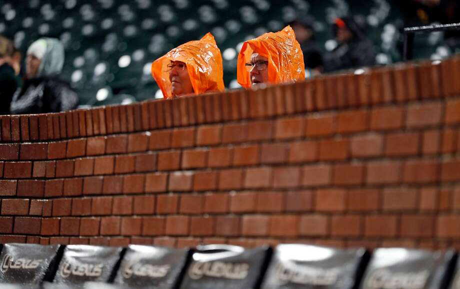 FILE – A pair of hardcore San Francisco Giants' fans brave the elements as they watch 5-4 loss to Oakland Athletics at Oracle Park in San Francisco in this Monday, March 25, 2019 file photo.The San Francisco Giants will be cutting prices for their season tickets for the first time since they moved into the ballpark now known as Oracle Park, according to a report from the San Francisco Chronicle, after a few years of attendance and season ticket sale drops. Photo: Scott Strazzante / The Chronicle