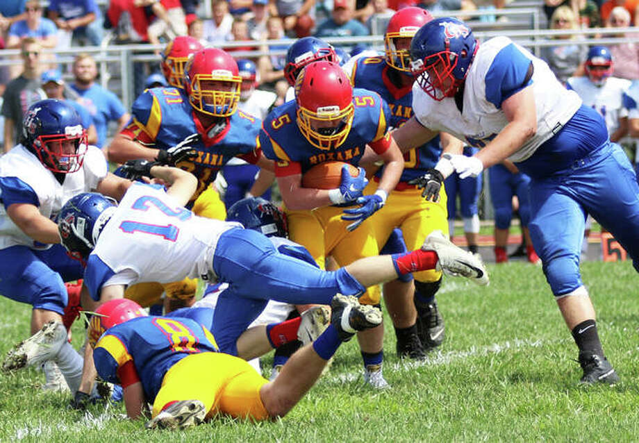 Roxana's Jacob Rexford (center) tries to navigate through heavy traffic with the football while Carlinville's 6-foot-4, 275-pound lineman Lane Stinnett (right) closes in to finish off the tackle Saturday at Raich Field in Roxana. The Shells are back home on Friday to play Pana, while Carlinville plays at home against Vandalia. Photo: Greg Shashack | The Telegraph