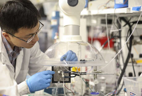 "Haotian Wang, an assistant professor of chemical and biomolecular engineering at Rice University, sets up an experiment with a carbon dioxide reduction reactor on Thursday, Sept. 5, 2019, in Houston. Wang said the device converts carbon dioxide into pure liquid fuel. ""We can only make very tiny contributions, but all of those tiny things add up and the momentum can be changed,"" Wang said, when asked about the technology's potential impact on climate change."