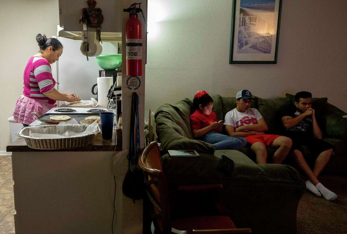 Marielena Palacios, center to right, and her older brothers Juan Jose, and Ariel, watch television as their mother, Jessica, makes dinner. After President Donald Trump rescinded the program that brought them here, the Palacios' boys now face sudden deportation.