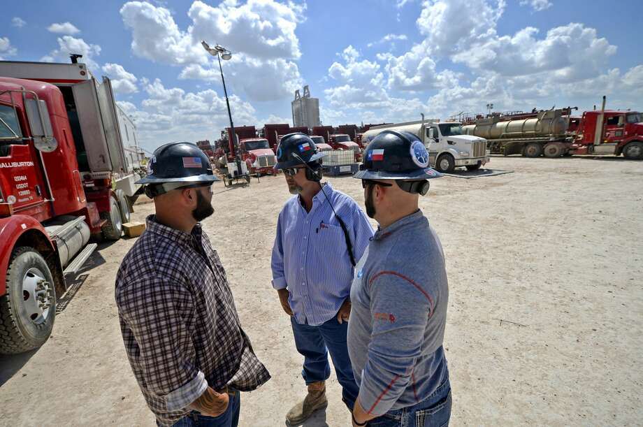"""From left, Octane Energy well-site leaders Justin """"Bull"""" Smith, Todd Greer, and Octane Energy CEO Jared Blong discuss operations on a fracking site managed by Octane Energy on Friday, Sept. 23, 2016 near Stanton. James Durbin/Reporter-Telegram Photo: James Durbin"""