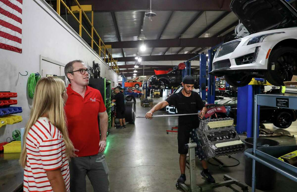 Warren Robinson, center, an external relations advisor for Royal Dutch Shell, smiles as he talks with Emma Hennessey Roys, left, the social media and events manager at Hennessey Performance, on Friday, Aug. 30, 2019, in Sealy. At right, Michael Crum, a technician, torques down the cylinder heads on an eight-cylinder LT4 engine.