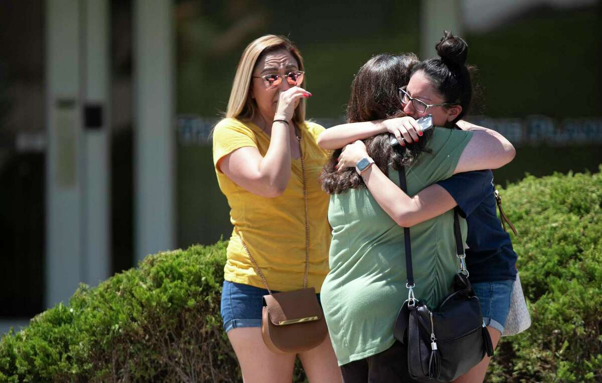 A family embraces near the Walmart where a man opened fire on back-to-school shoppers, Saturday, August 3, 2019, in El Paso, Multiple people are dead after a mass shooting at an El Paso Walmart on Saturday. The mayor says three people are in custody for the shooting but the El Paso police spokesman says there was only one shooter.