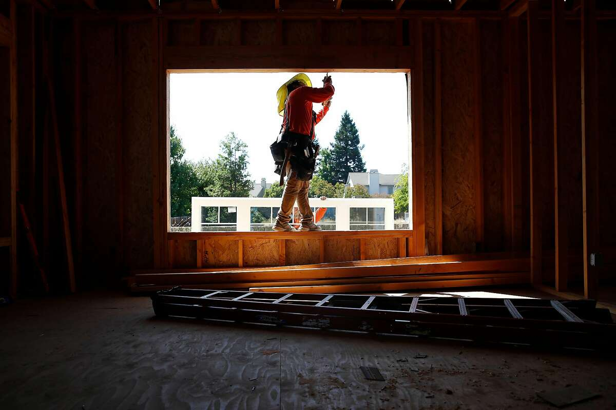Andrew Gonzalez (foreground) and Juan Macias (background), laborers Wolff Contracting, �work to install a window in the the accessory dwelling unit Michael Wolff (not shown), owner Wolf Contracting, is building for his father on Wednesday, September 4, 2019 in Santa Rosa, CA.