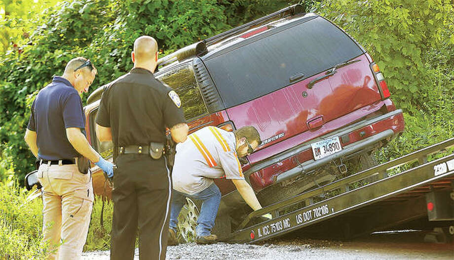 An Alton Police detective, left, photographed the vehicle before it was towed away for police by Fred's Towing at the dead end of Thomas Street.