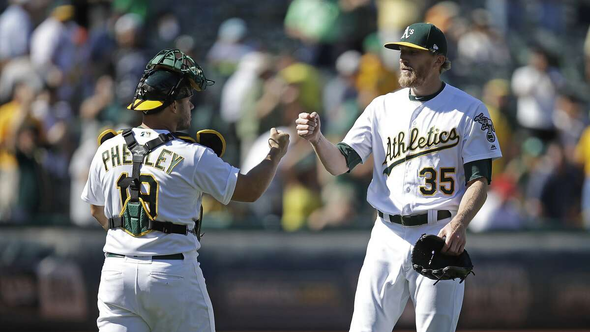 Oakland Athletics' Jake Diekman, right, celebrates with catcher Josh Phegley, left, at the end of a baseball game against the Los Angeles Angels, Thursday, Sept. 5, 2019, in Oakland, Calif. (AP Photo/Ben Margot)