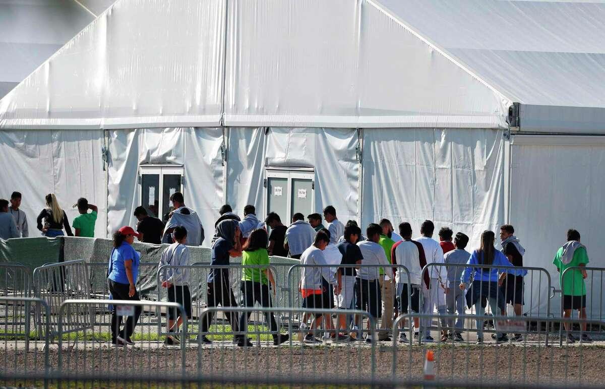 ARCHIVO - Menores de edad hacen cola para ingresar a una carpa en el Albergue Temporal de Menores No Acompañados en Homstead, Florida, el 19 de febrero del 2019.