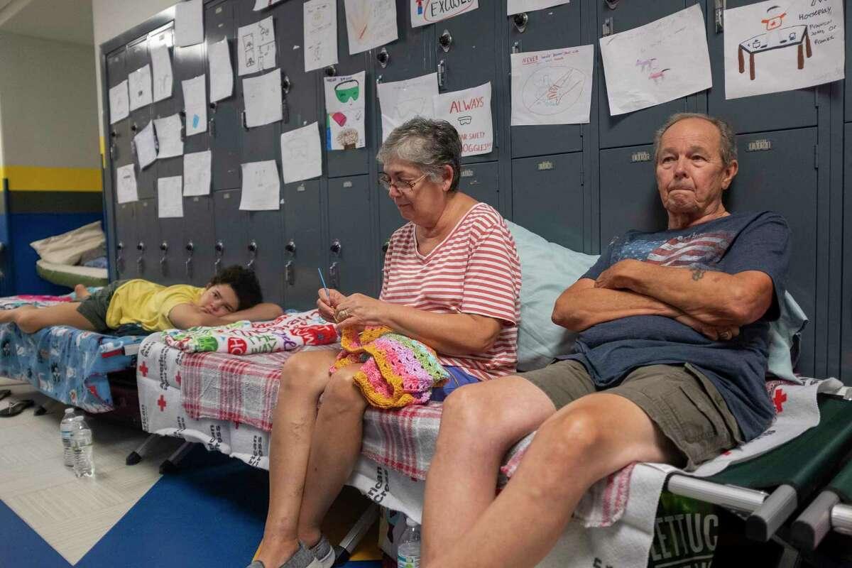 Gordon y Dina Reynolds, junto a su hija de 11 años, Abby, sentados en catres en el pasillo de la escuela secundaria North Myrtle Beach, que se está utilizando como refugio de evacuacón de Cruz Roja el miércoles 4 de septiembre de 2019.