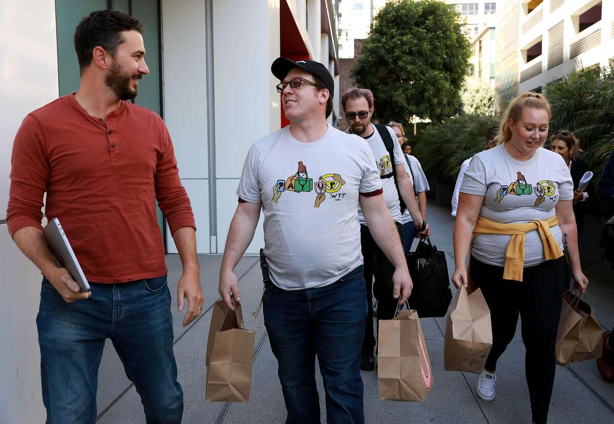 Keith Chapman, left, converses with Felix Sanchez, second from left, as Tyler Breisacher and Vanessa Bain walk with them outside of the Postmates headquarters at 201 Third St. in San Francisco, Calif., on Thursday, September 5, 2019. Workers from Postmates, DoorDash, and Instacart rallied outside these companies' corporate headquarters to deliver messages calling for new laws and policies. They also held bags of peanuts, since they say they are paid peanuts.