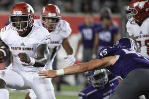 North Shore quarterback Dematrius Davis, left,  avoids the tackle of Ridge Point defensive end Carter Aycock en route to a touchdown during the second half of a high school football game, Thursday, Sept. 5, 2019, at TDECU Stadium at the University of Houston.