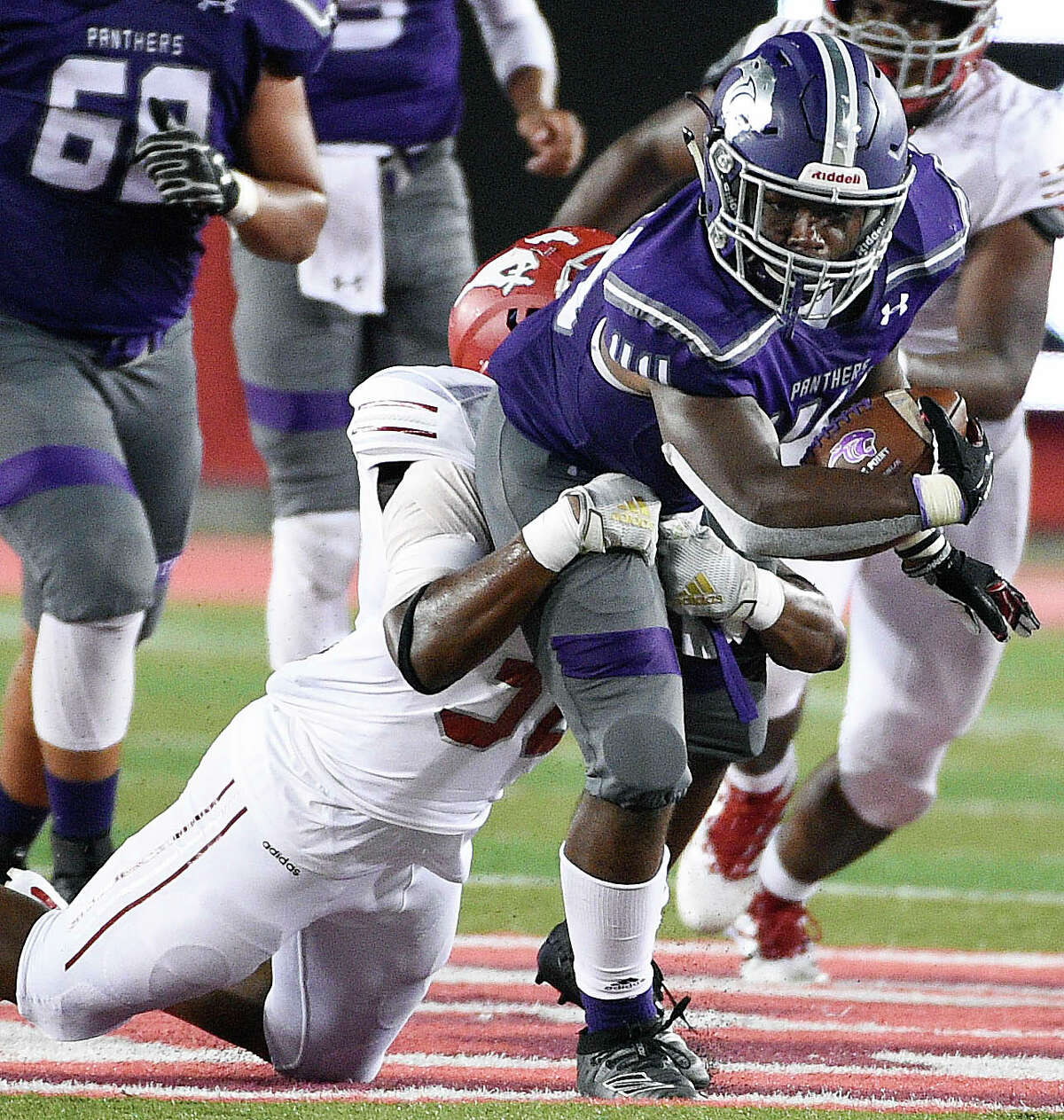 Ridge Point running back Marcus Wright, right, is tackled by North Shore linebacker Jermaine Caldwell during the second half of a high school football game, Thursday, Sept. 5, 2019, at TDECU Stadium at the University of Houston.