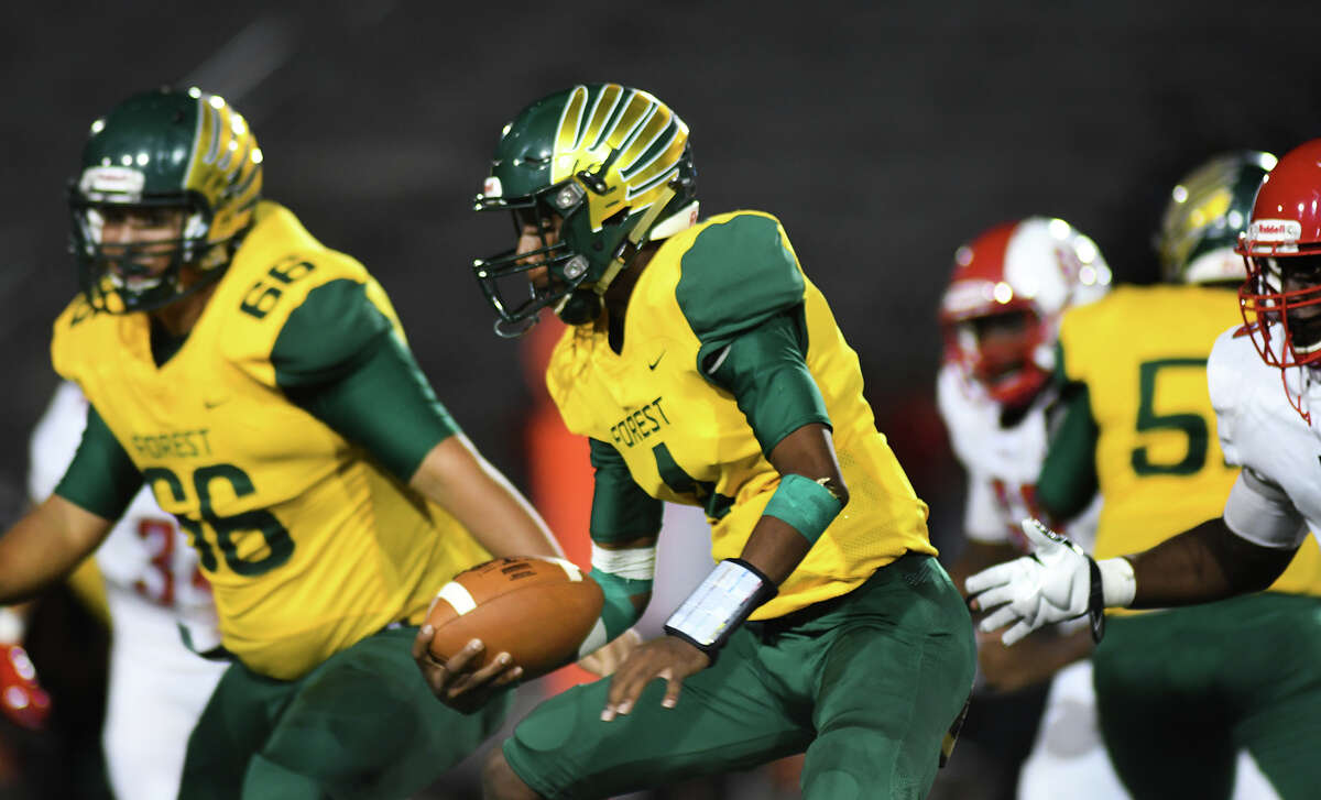 Klein Forest senior quarterback Myles Rhodes (4) works for yardage behind a block from junior teammate Roberto Rios (66) late in the 4th quarter of their matchup at Klein Memorial Stadium on Sept. 5, 2019.