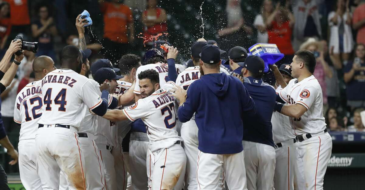 Houston Astros Jose Altuve (27) was among those celebrating with Michael Brantley after his walk off home run to beat the Seattle Mariners 11-9 during the thirteenth inning of an MLB game at Minute Maid Park, Thursday, September 5, 2019, in Houston.