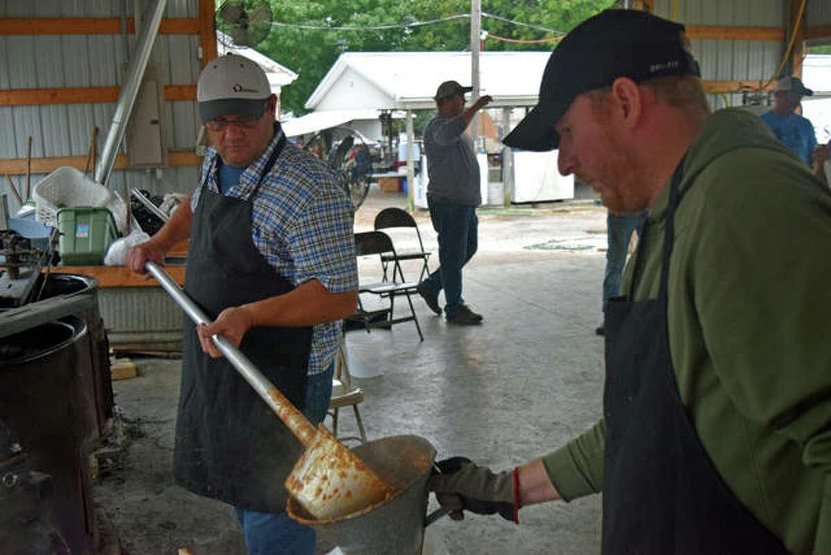 Volunteers Brian Burrus and Matt Petefish ladle soup for visitors during the 2018 Arenzville Burgoo.