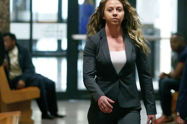 FILE - In this March 18, 2019 file photo, former Dallas Police officer Amber Guyger walks the hallway on her third court appearance at the Frank Crowley Courts Building in Dallas. Jury selection is set to begin, Friday, Sept. 6, in the trial of Guyger, charged with killing an unarmed black man in his own apartment. Guyger faces a murder charge in the slaying of Botham Jean. Guyger told authorities she mistakenly entered Jean's apartment thinking it was her own and fatally shot him. (Vernon Bryant/The Dallas Morning News via AP, File)