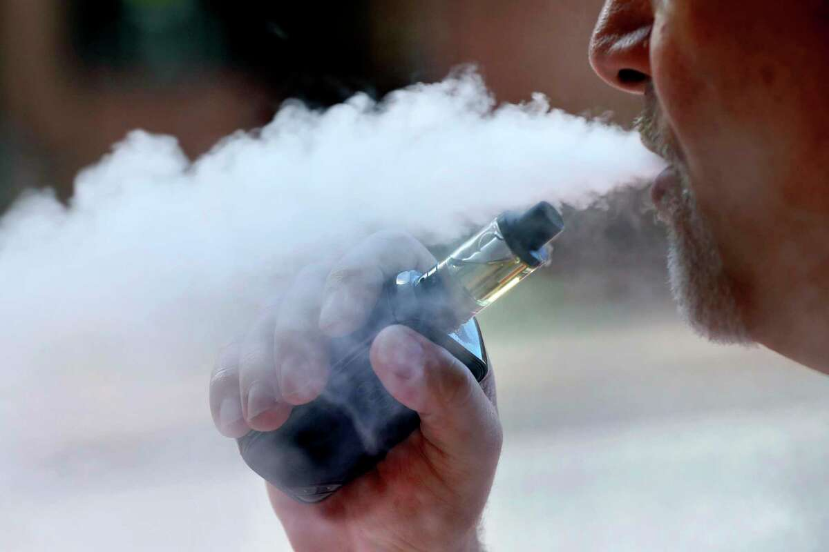 A man exhales while smoking an e-cigarette.