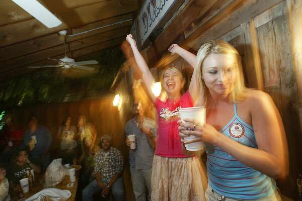 (LEFT TO RIGHT) Lemoine Knox, 20, encourages her hometown friend Tina Hall, 22, of Coleman Texas, to finish drinking her 'chugger' where Tina dunked her graduation ring at the popular Dixie Chicken in College Station. Texas A&M University-College Station distributed approximately 3,500 graduation rings to students at the Clayton W. Williams, Jr. Alumni Center. Photo by Mayra Beltran/ Houston Chronicle