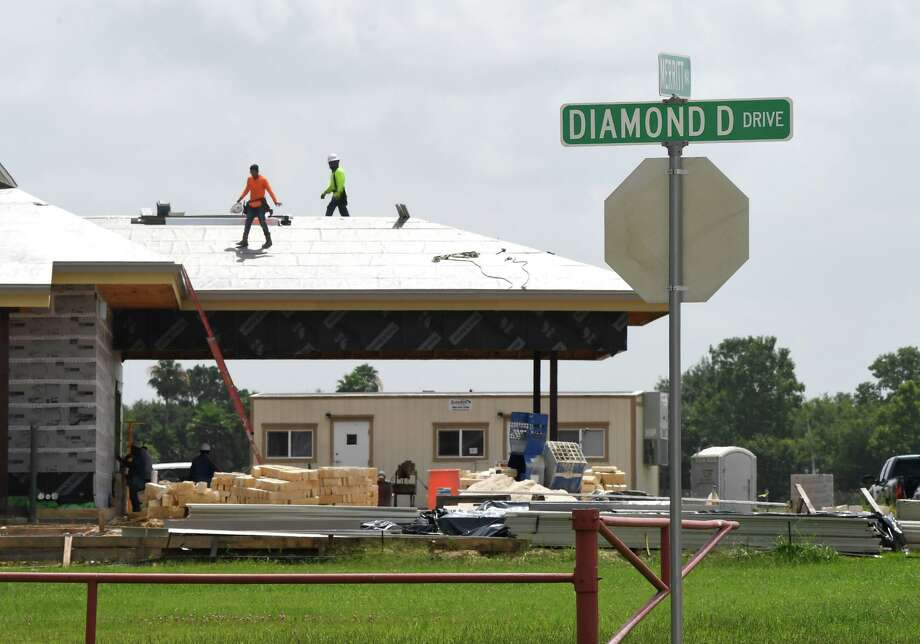 Workers install the roof on the Liberty Bank being constructed in front of the Diamond D Ranch on Friday. Photo taken Friday, 6/28/19 Photo: Guiseppe Barranco/The Enterprise, Photo Editor / Guiseppe Barranco ©