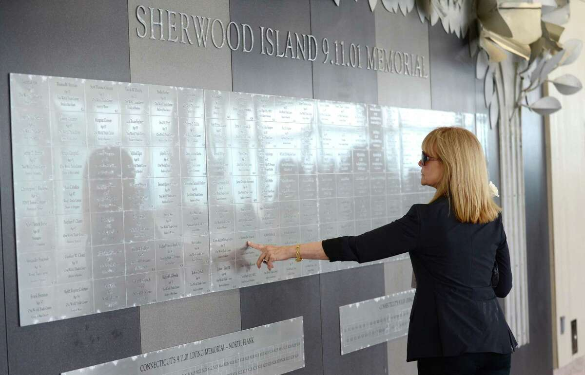 Former flight attendant Sari Weatherwax, who lost co-workers on 9/11, touches the names at the memorial.