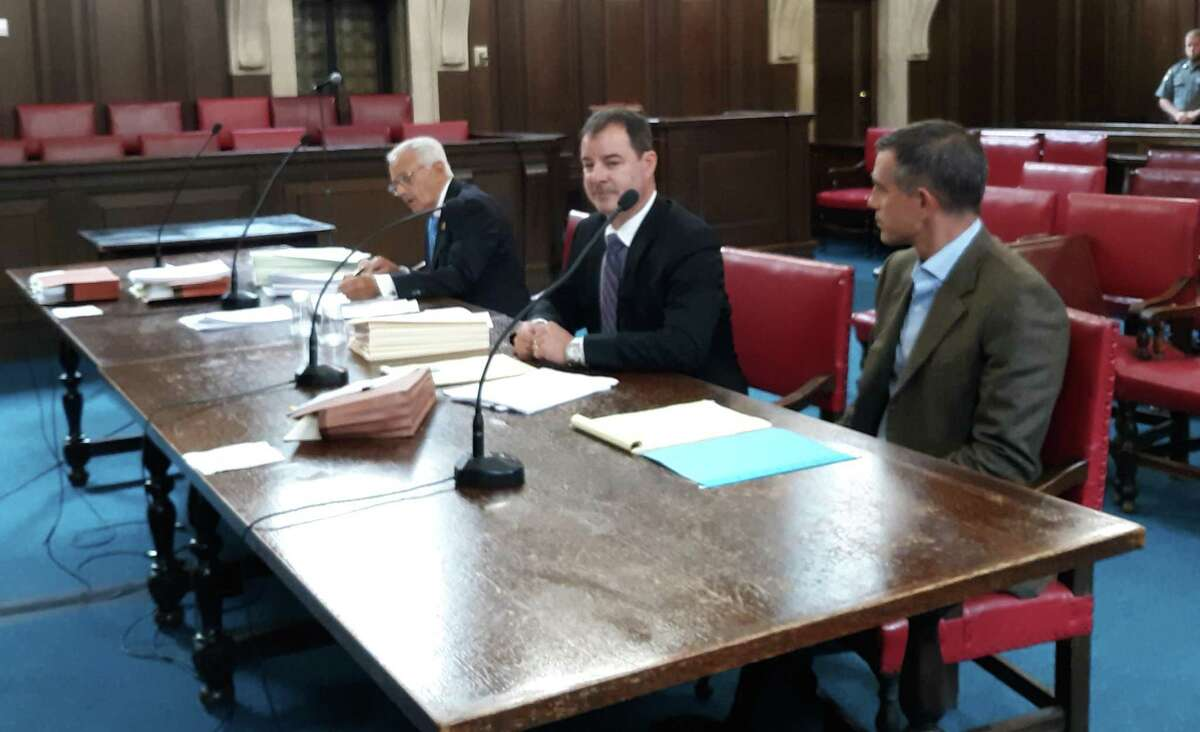 Attorney William Murray, center, with his client, Fotis Dulos, at a hearing Friday at Hartford civil court.
