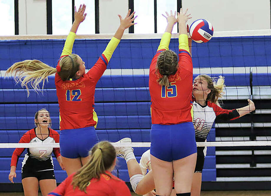 Bunker Hill's Makenna Wilkinson (right) gets a kill off the block of Roxana's Abbi Zangori (15) with the Shells' Olivia Mouser also contesting the attack during a Minutemaids' loss Aug. 26 at the Roxana Tourney. The Maids have recovered from a 0-2 start to win four in a row with Thursday's victory at Gillespie. Photo: Greg Shashack / The Telegraph