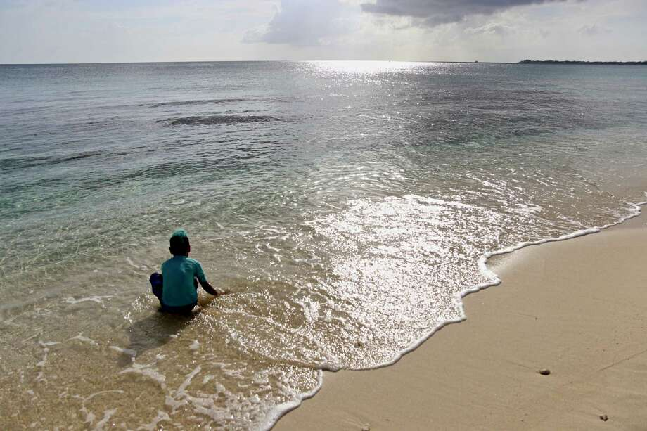 The author's son Zephyr Martell, 6, plays in the Caribbean Sea on Grand Cayman's Seven Mile Beach. Photo: Photo For The Washington Post By Nevin Martell / Nevin Martell