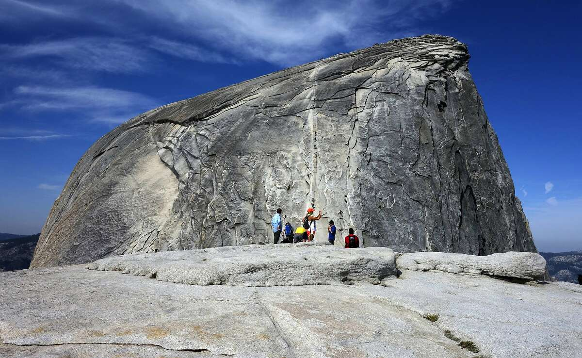 In this July 15, 2014, file photo, hikers gather in the foreground as climbers use the assistance of cables to scale Half Dome in Yosemite National Park National Park in California's Sierra Nevada. A hiker in Yosemite National Park fell to his death while climbing to the top of iconic granite cliffs of Half Dome. Park spokesman Scott Gediman says 29-year-old Danielle Burnett, of Lake Havasu City, Arizona, was scaling the steepest part of the trail Thursday, Sept. 5, 2019, when she fell more than 500 feet down the steep, rocky terrain. Gediman says Burnett was dead when park rangers arrived on the scene.