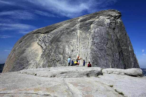 File - In this July 15, 2014, file photo, hikers gather in the foreground as climbers use the assistance of cables to scale Half Dome in Yosemite National Park National Park in California's Sierra Nevada. A hiker in Yosemite National Park fell to his death while climbing to the top of iconic granite cliffs of Half Dome. Park spokesman Scott Gediman says 29-year-old Danielle Burnett, of Lake Havasu City, Arizona, was scaling the steepest part of the trail Thursday, Sept. 5, 2019, when she fell more than 500 feet down the steep, rocky terrain. Gediman says Burnett was dead when Park Rangers arrived on the scene. (AP Photo/Brian Melley, File)
