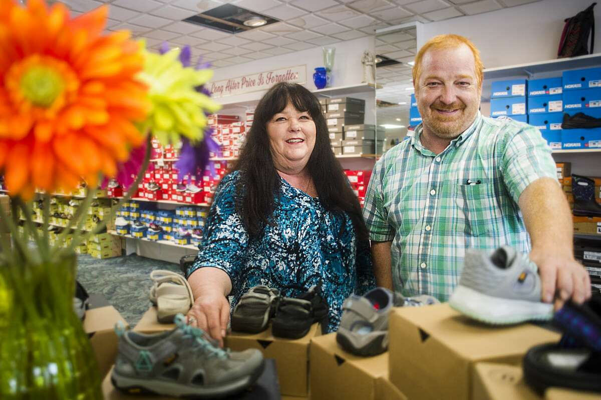 Renee Pinnow, left, and Andy McGee, right, pose for a portrait inside Circle Quality Shoes, which was named the 2019 Readers' Choice best place to buy shoes. Second place went to Kohl's and third place went to Little Forks Outfitters. (Katy Kildee/kkildee@mdn.net)