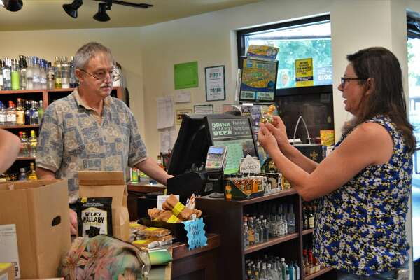 Ernest Isberg cashes out Michelle Kirsch, who admires a mini Patron bottle, at the Eastman Party Store. Eastman Party Store won two Readers' Choice awards for 2019: Best place to buy carryout wine and best place to buy carryout beer. (Ashley Schafer/Ashley.schafer@hearstnp.com)