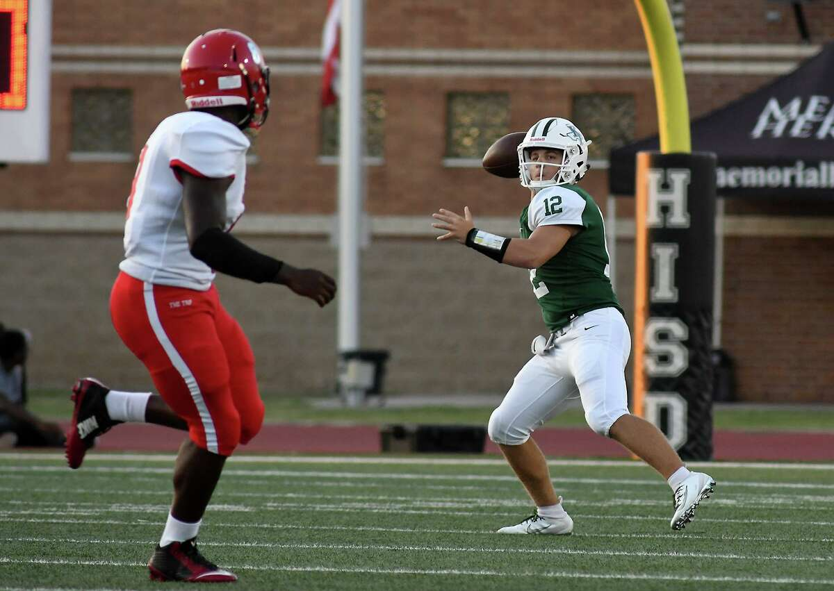 Kingwood Park junior quarterback Hudson Dezell (12) works for a receiver against a Waltrip defender in the 1st quarter of their matchup at Turner Stadium in Humble on Sept. 5, 2019.