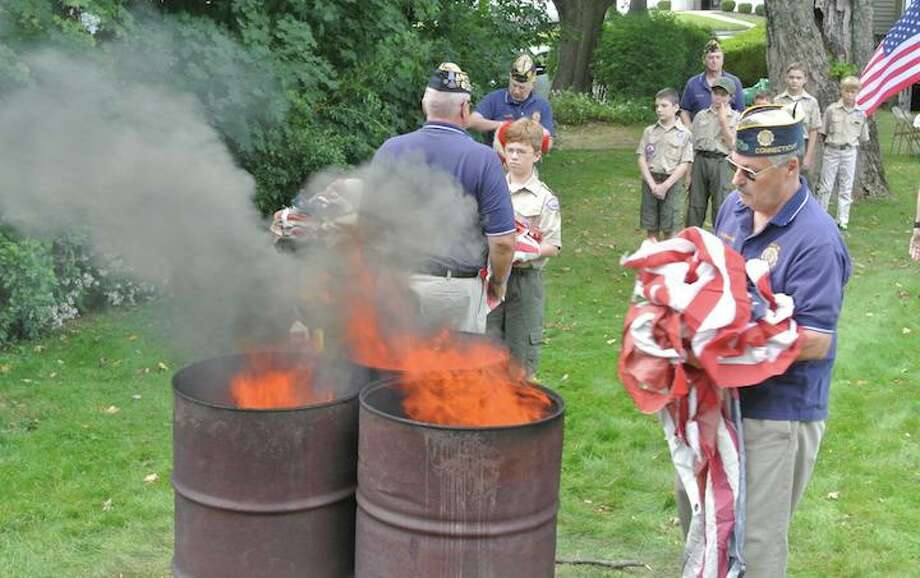 Don Hazzard, of American Legion Post 86, prepares to burn worn out American flags during a formal flag retirement ceremony. The post will hold this year's ceremony on Sept. 15. Photo: Jeannette Ross / Hearst Connecticut Media / Wilton Bulletin