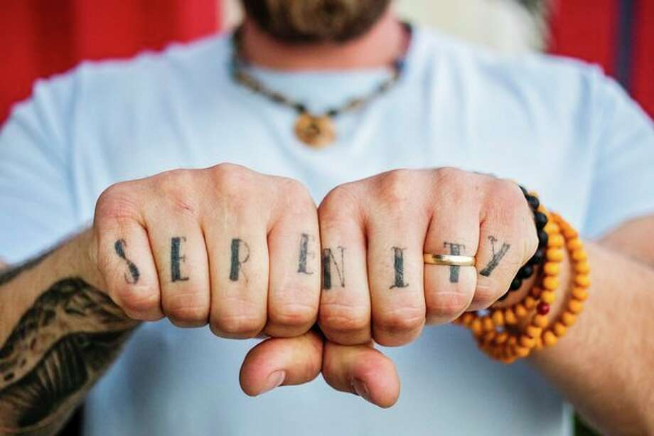 """Zachary Brewer displays his knuckle tattoo, which reads """"serenity,"""" as he poses for a portrait Thursday in Bay City. (Katy Kildee/kkildee@mdn.net)"""
