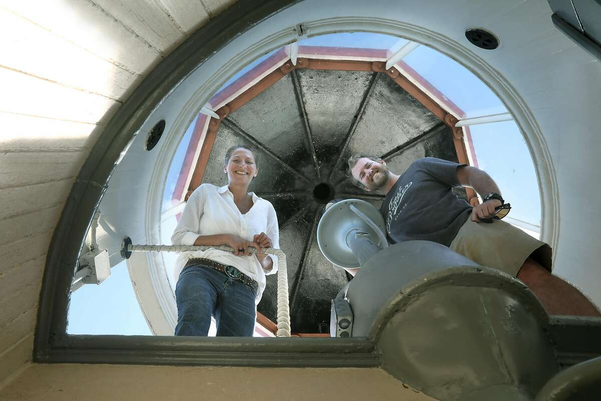 Innkeepers Tiffany Danse (left) and Tyler Waterson (right) show the lighthouse as they surround the lamp at the East Brother Light Station located on a small island just off Point San Pablo Harbor on Tuesday, July 23, 2019 in Richmond, Calif.