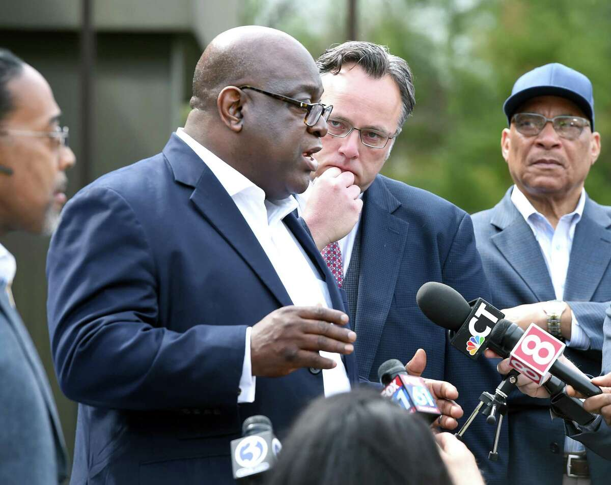 Hamden Mayor Curt Leng (center right) listens to Rev. Boise Kimber (center left) address the media outside of the Hamden Government Center on April 19, 2019 after a meeting between the town officials and local clergy concerning the recent shooting by a Hamden police officer.