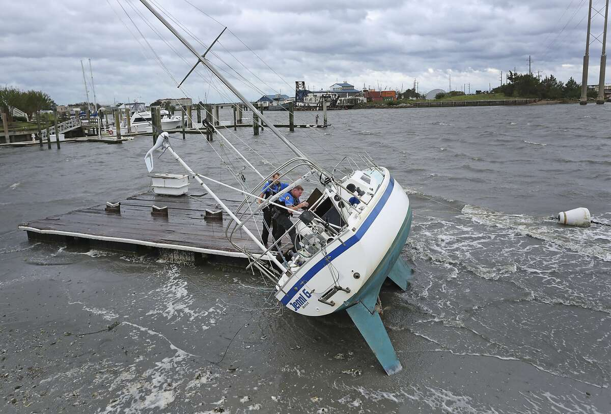 Beaufort Police Officer Curtis Resor, left, and Sgt. Micheal Stepehens check a sailboat for occupants in Beaufort, N.C. after Hurricane Dorian passed the North Carolina coast on Friday, Sept. 6, 2019. Dorian howled over North Carolina's Outer Banks on Friday - a much weaker but still dangerous version of the storm that wreaked havoc in the Bahamas - flooding homes in the low-lying ribbon of islands and throwing a scare into year-round residents who tried to tough it out. (AP Photo/Tom Copeland)