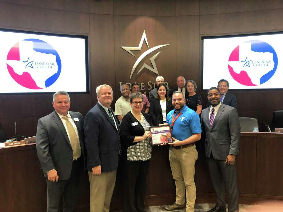 Quentin Wright, second from the right, receives a community champion award from the Aldine-Greenspoint YMCA at the September meeting of the Lone Star College Board of Trustees. Photo: Bill Van Rysdam