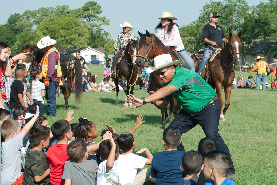 Pasadena ISD Associate Superintendent Joe Saavedra greets children at Sparks Elementary during the Pasadena Rodeo trail ride Friday, Sep. 6. Photo: Kirk Sides/Staff Photographer